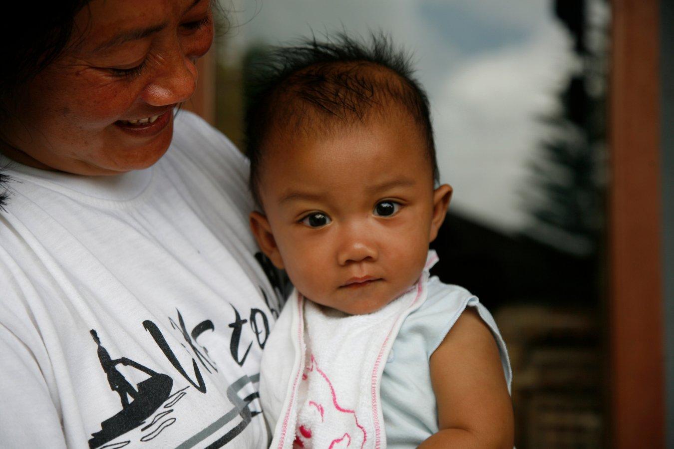 Een kind met zijn SOS mama in één van onze kinderdorpen in Indonesië